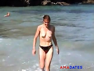 girl topless on beach with small empty saggy boobs