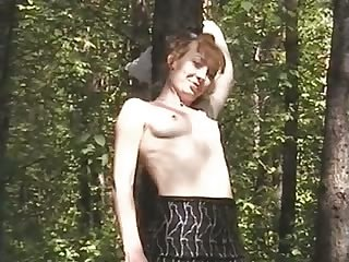 Pallid redhead exposes tits and giggles as she pisses in the forest